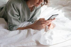 Pige på senge med mobil
